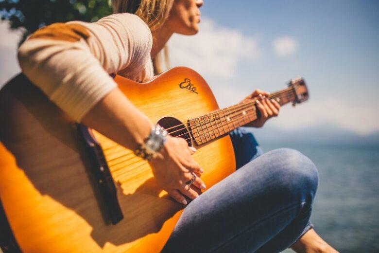 blonde-woman-playing-guitar-at-seaside