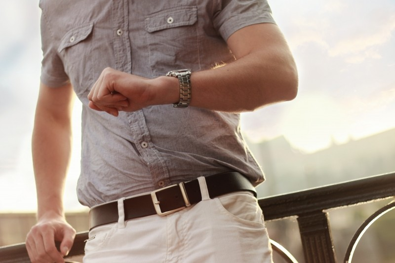 man-leaning-against-railing-and-checking-watch